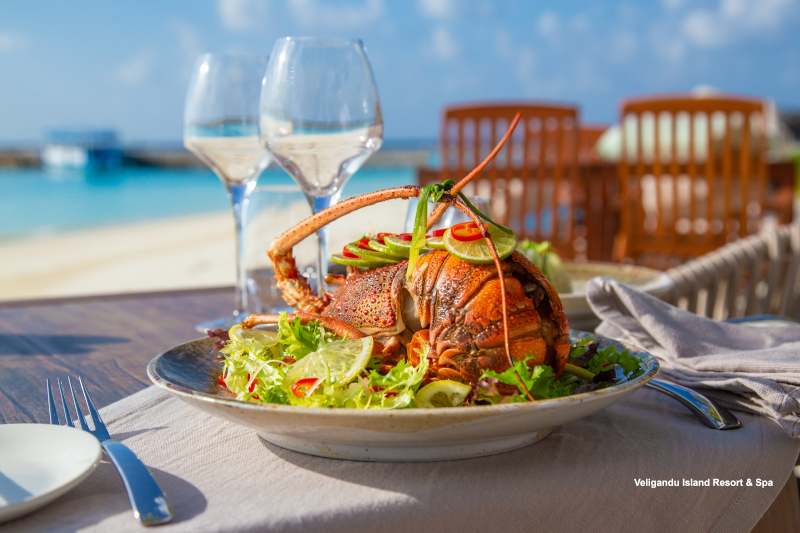 Dining at Veligandu Island Resort & Spa Hand-dived baked lobster served with lagoon views at Madivaru à la carte restaurant